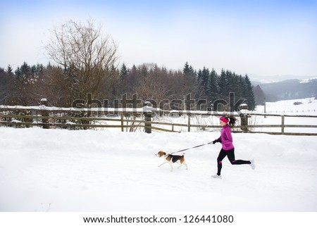 Athlete woman is running during winter training outside in cold snow weather. - stock photo