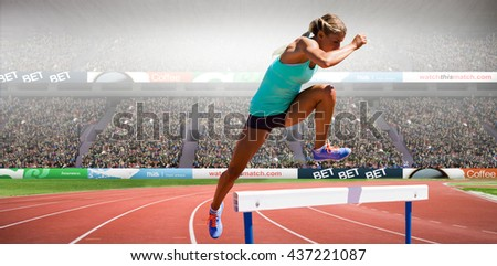 Athlete woman jumping a hurdle against view of a stadium