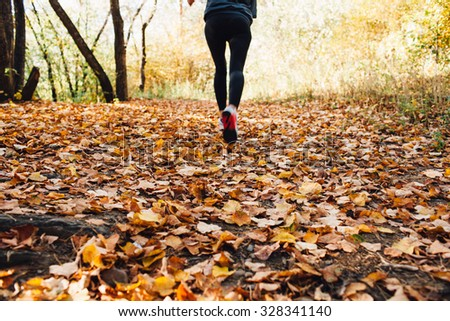 athlete woman runs for fall foliage, shoes closeup