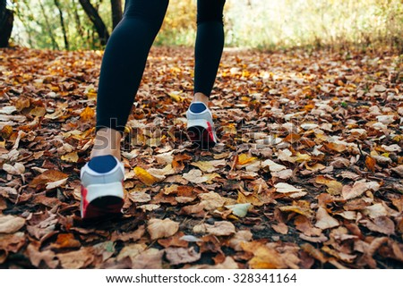 athlete woman runs for fall foliage, shoes closeup, back view - stock photo