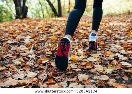 athlete woman runs for fall foliage, shoes closeup, back view