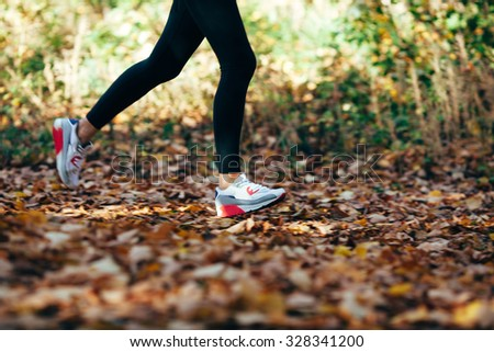 athlete woman runs for fall foliage, shoes closeup, motion blur effect - stock photo
