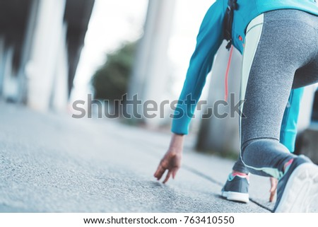 Athlete Young Girl In Running Start Pose On The City Street Morning Sport