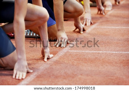 Athletes at the sprint start line in track and field - stock photo