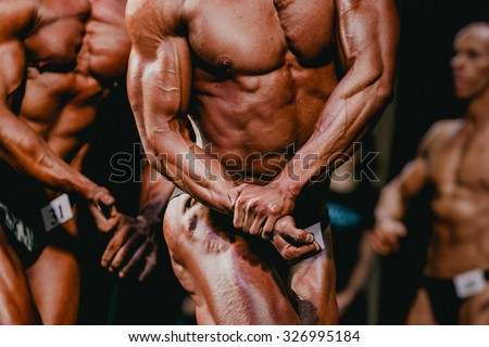 athletes bodybuilders are straining biceps side of arm - stock photo