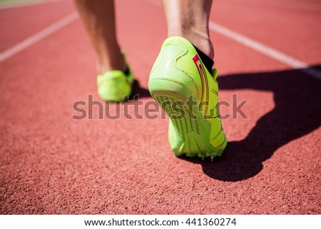 Athletes feet running on the racing track on a sunny day