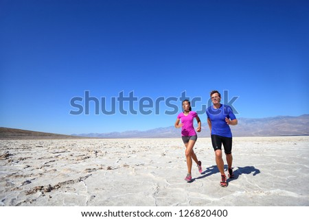 Athletes running sport fitness couple outdoor. Multiracial couple of runners training outdoors in fitness clothing under burning sun in desert. Caucasian man runner and Asian woman training. - stock photo