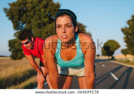 Athletes taking a rest after road running race or marathon. Tired female runner and man resting and breathing. Sport motivation and lifestyle concept. - stock photo