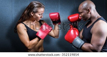 Athletes with fighting stance against dark grey room