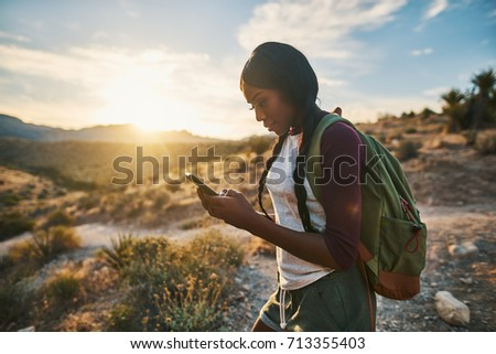 athletic african american woman with backpack looking at smart phone while hiking in red rock canyon nevada