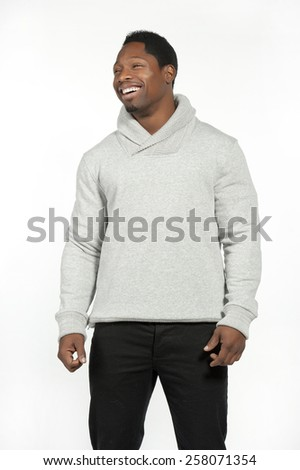 Athletic and attractive black male wearing a fitted gray sweater with black pants in a studio setting on a white background posing and laughing and looking to the left.