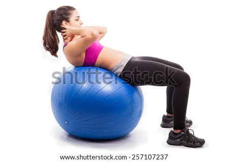 Athletic and strong young woman doing some crunches on an exercise ball on a white background