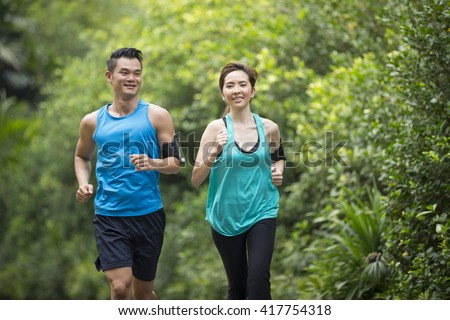 Athletic Asian man and woman running outdoors. Action and healthy lifestyle concept. - stock photo