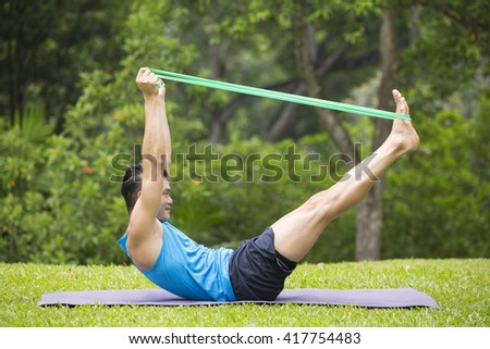 Athletic Asian man exercising with a resistance band. Action and healthy lifestyle concept.