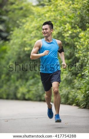 Athletic Asian man running outdoors. Action and healthy lifestyle concept. - stock photo
