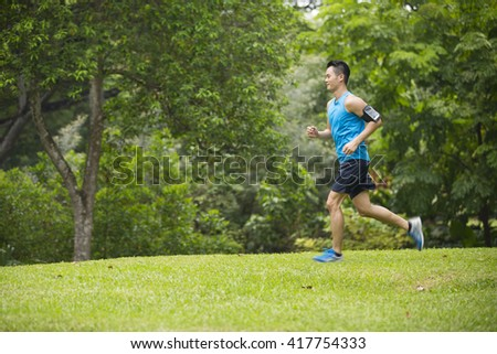 Athletic Asian man running outdoors. Action and healthy lifestyle concept.
