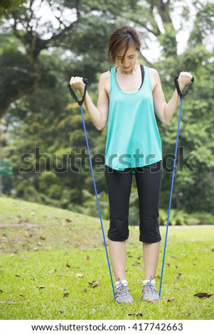 Athletic Asian woman exercising with a resistance band. Action and healthy lifestyle concept.