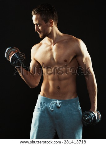 Athletic attractive man with dumbbells on the black background - stock photo
