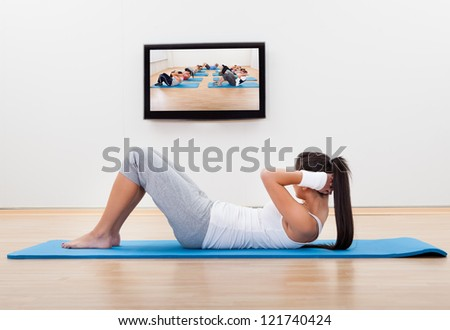 Athletic barefoot young woman working out at home lying on a mat doing liftups and head raises while watching and participating in a class - stock photo