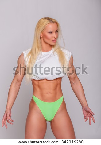 Athletic blond woman in green panties and white t shirt. - stock photo