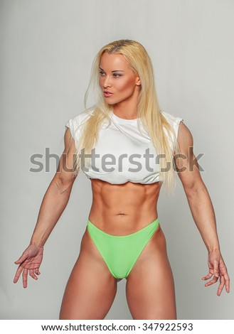 Athletic blond woman in green panties and white t shirt.
