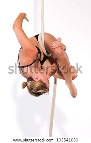 Athletic blonde aerialist suspended from a rope