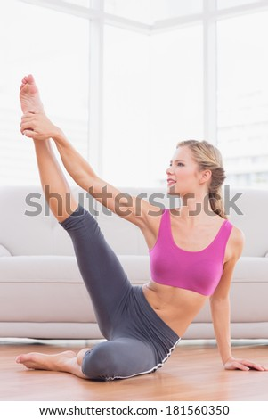Athletic blonde sitting on floor stretching leg up at home in the living room - stock photo