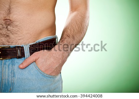 athletic body with blue jeans close up isolated on green