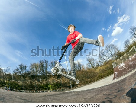 athletic boy jumping with a scooter over a funbox