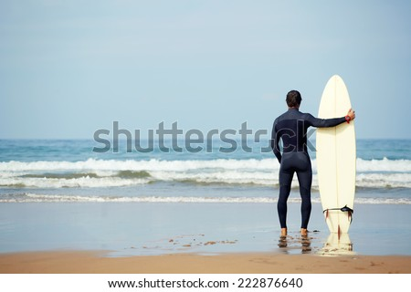 Athletic build young surfer holding surfboard while standing on the beach looking at ocean to find the perfect spot to go surfing waves, professional surfer waiting waves on the ocean beach - stock photo
