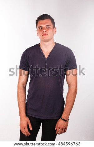 Athletic Caucasian man standing in a violet purple shirt in the studio isolated on white background looking at the camera pose, serenity, confidence