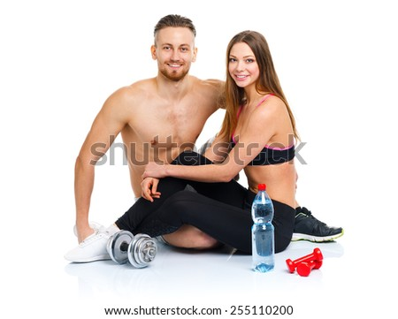 Athletic couple - man and woman after fitness exercise with dumbbells and bottle of water sitting on the white background - stock photo