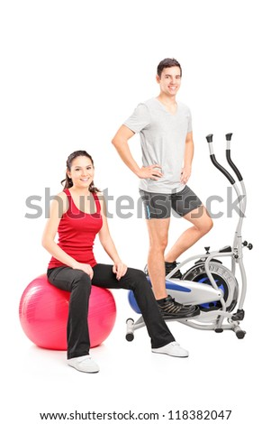 Athletic couple posing with a fitness equipment, cross trainer machine and pilates ball, isolated on white background