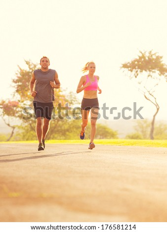 Athletic couple running together at Sunrise. Sport runners jogging on park trail in the early morning.  Healthy lifestyle fitness concept - stock photo