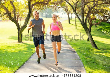 Athletic couple running together. Sport runners jogging on park trail in the early morning.  Healthy lifestyle fitness concept - stock photo