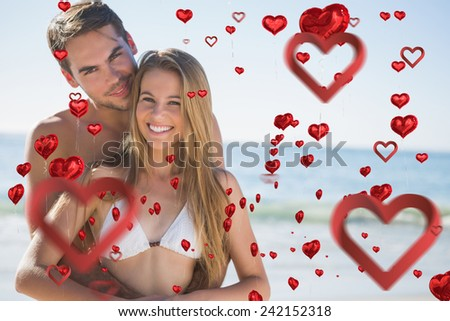 Athletic couple smiling at camera and embracing against love heart pattern - stock photo