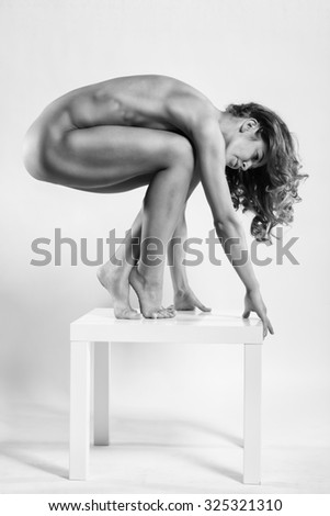 Athletic European fashion model woman with shiny curly hair, awesome gorgeous slim body and perfect skin is sitting on the table nude in studio for bodycare and wellness adverisement. - stock photo