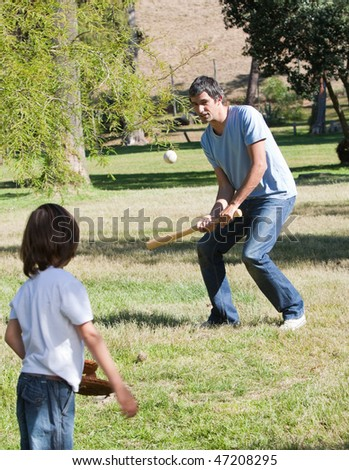 Athletic father playing baseball with his son in the park - stock photo