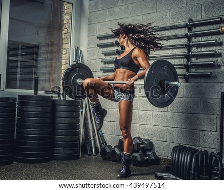 Athletic female in casual sportswear doing workouts with barbell in a gym club. - stock photo