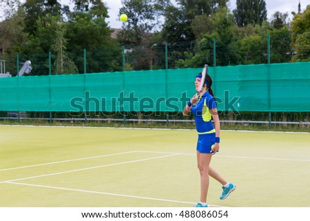 Athletic female tennis player wearing a sportswear warming up before tennis match on a court outdoor in summer or spring
