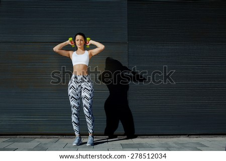 Athletic female with perfect figure getting her arms in great shape while lifting weights up, attractive young woman using dumbbells to work out arms while training outdoors on copy space background - stock photo