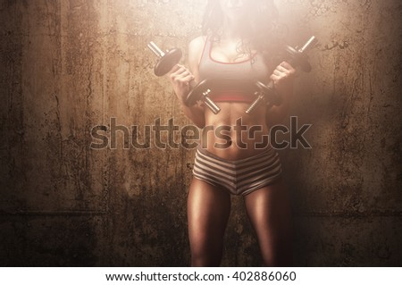 Athletic fitness model training with dumbbells in front of concrete textured wall showing her abs and muscles