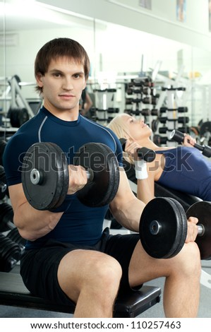 athletic girl and guy,  exercise with dumbbells and smile, in  sport-hall