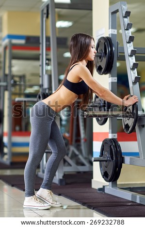 Athletic girl doing exercises with barbell in gym. Attractive fitness woman, trained female body. Brunette sexy fitness girl in black and gray sport wear with perfect body in the gym.