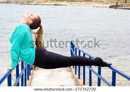 Athletic girl doing stretching exercise outside near crossbar, spring time - stock photo