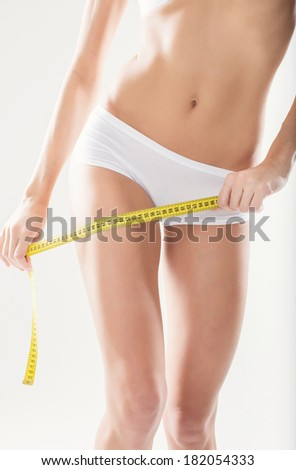 Athletic girl measuring yourself figure yellow meter