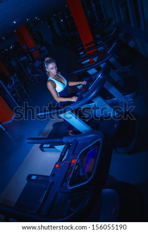 athletic girl on treadmill at gym shouted with studio flashes - stock photo