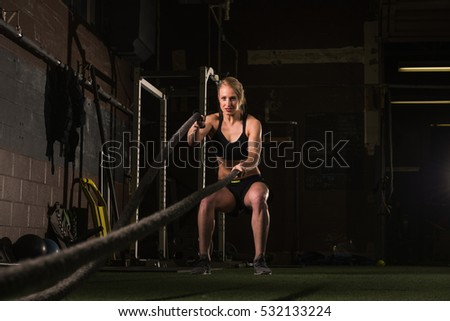 Athletic girl working out with a rope at gym