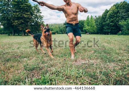 athletic guy with a German Shepherd