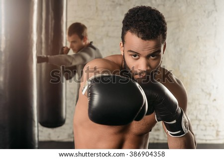 Athletic guy with naked torso in boxing gloves, boxing in the loft gym, boxing guy, black punching bags in the background - stock photo